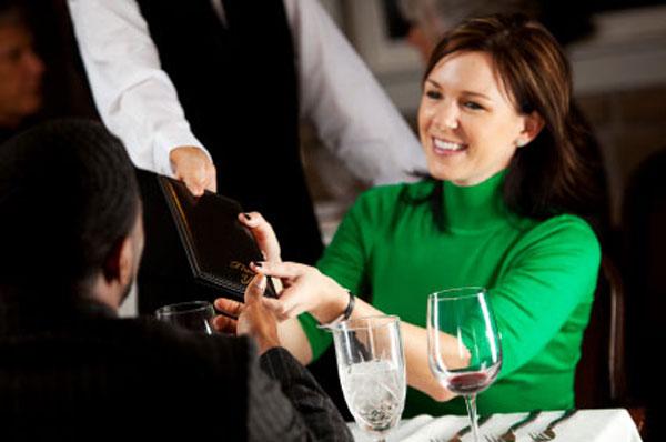 mujer vestida de verde sentada recibiendo la cuenta para pagarla y entregarla al mesero