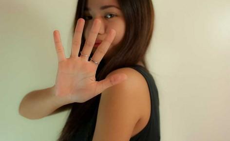 mujer usando una blusa negra y levantando la mano