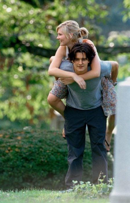 personas en medio de un jardín mientras el hombre carga a la mujer en los hombros