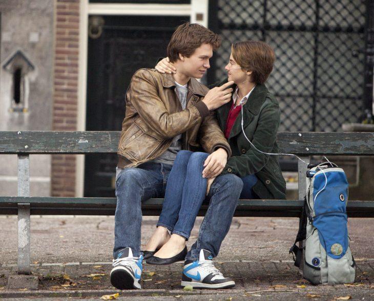 pareja sentada en una banca, ella con un respirador artificial