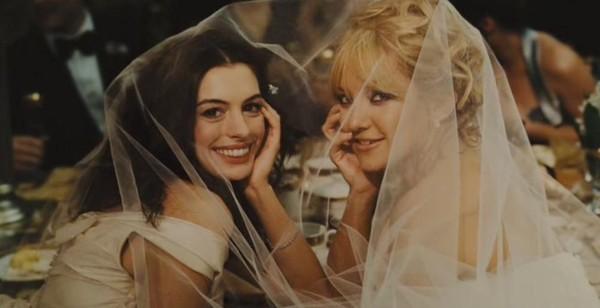 novias sonriendo sentadas en una silla cubiertas por un velo de novia