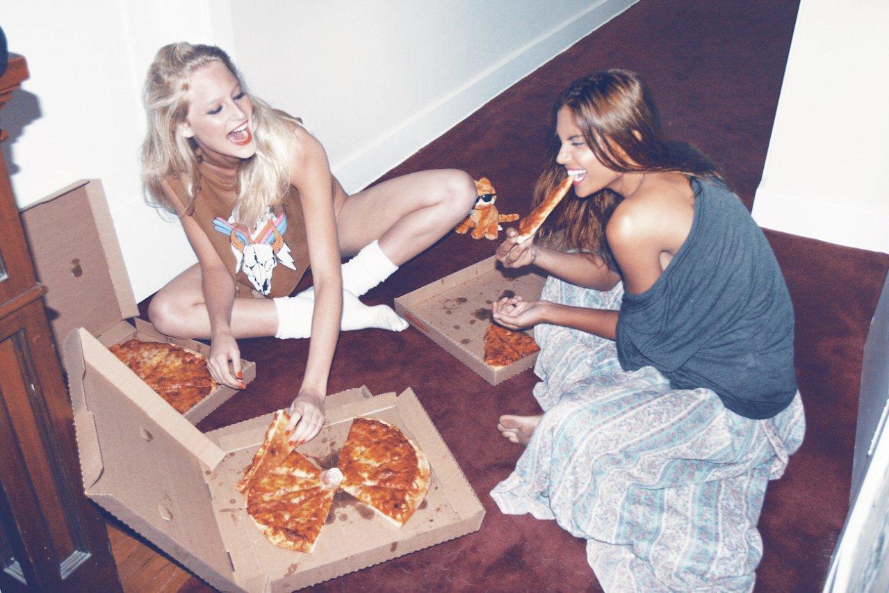 chicas sentadas en el suelo comiendo pizza