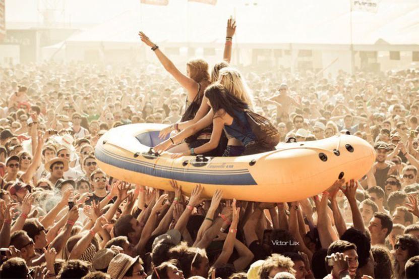 chicas en un concierto arriba de una lancha cargada por un mar de gente