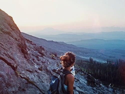 chica en una montaña con mochila