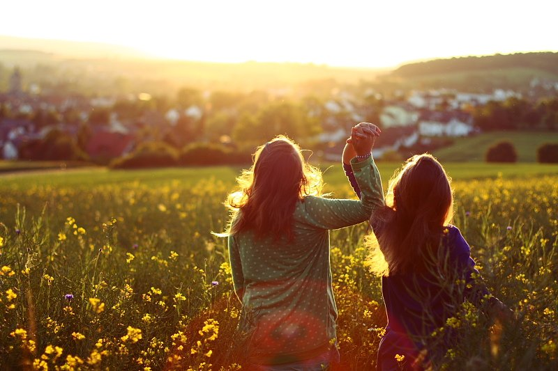 hermanas agarradas de la mano en el campo viendo el atardecer