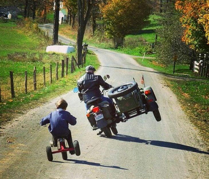 niño imitando a su padre en una motocicleta