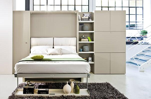 cama de color claro con decoraciones de jarrones y libros