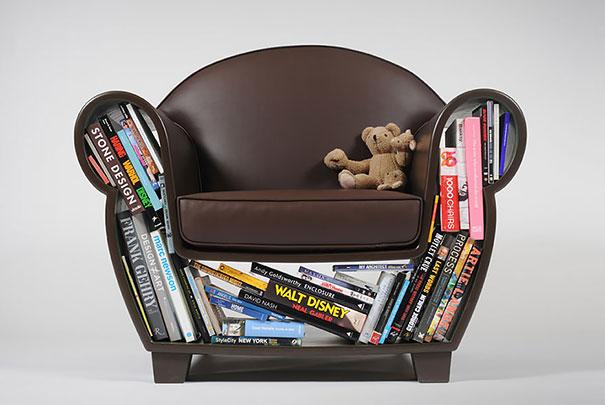 sofá con distintos libros y un oso de felpa sobre el