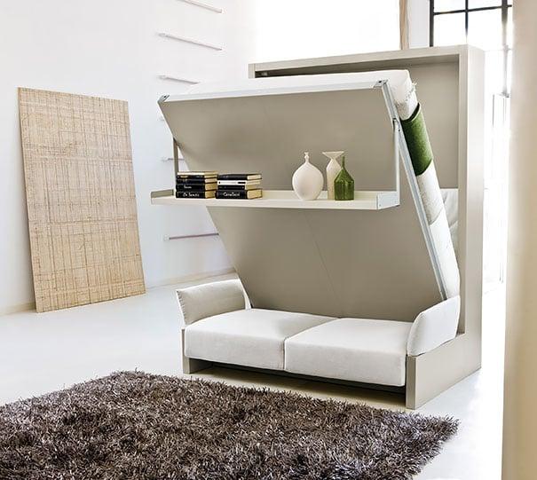 sofa cama que tiene decoraciones de jarrones y libros
