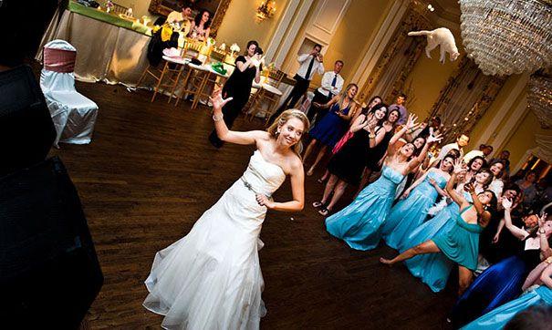 mujer vestida de novia en medio de la pista de baile lanzando un gato al aire el día de su boda