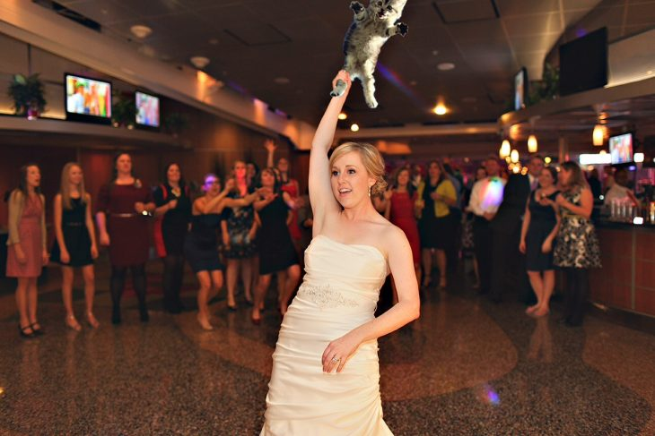 Novia en medio de una pista de baile mientras sostiene a un gato de una pata esperando lanzarlo a sus amigas que están a un lado de la barra de bebidas