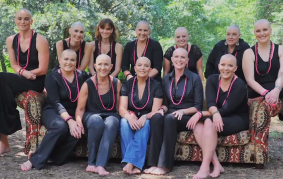 grupo de amigas con la cabeza rapada vestidas de negro con collares rosa
