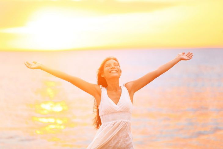 mujer feliz cno los brazos abiertos sonriendo en la playa