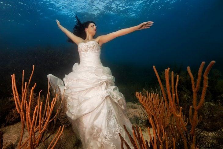 novia bajo el agua con brazos extendidos