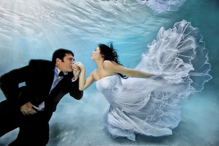 foto de novios bajo el agua tomados de la mano