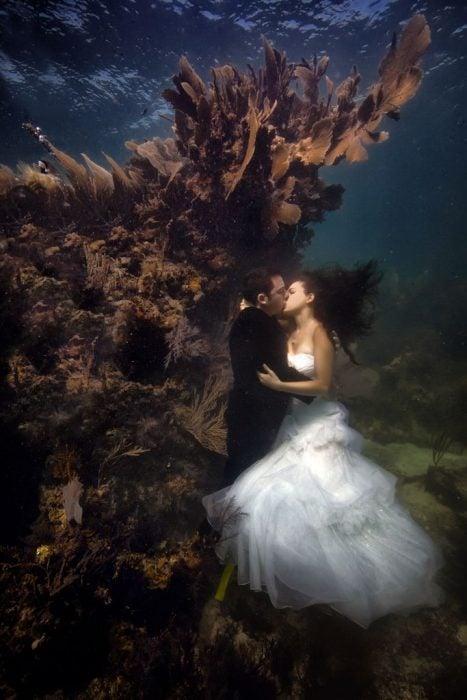 novios besandose bajo el agua
