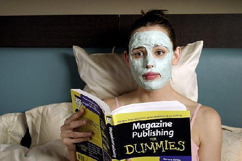 mujer sentada en la cama usando una mascarilla mientras lee un libro de publicidad para tontos