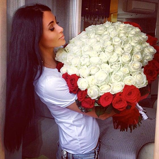 chica de cabello largo cargando un ramo gigante de rosas blancas