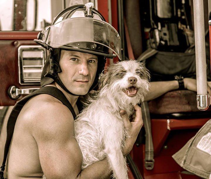 Bombero junto a un camión cargando un perro