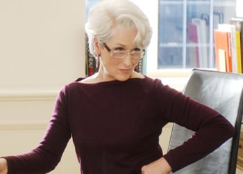 mujer de cabello blanco que usa lentes y esta vestida con blusa color uva