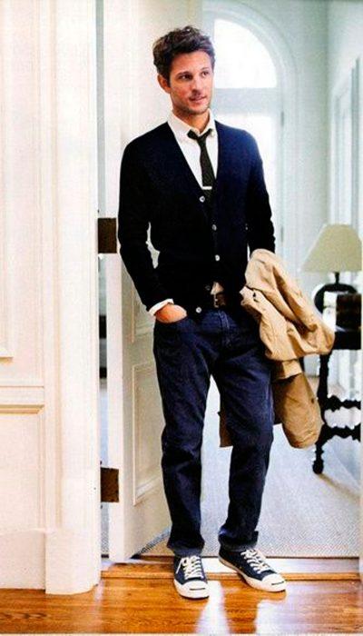 hombre parado afuera de una habitación sosteniendo en una mano una chaqueta