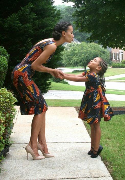 madre e hija usando el mismo vestido paradas en medio de la calle