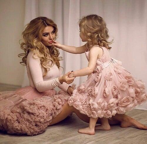 madre e hija sentadas usando un vestido de color rosa