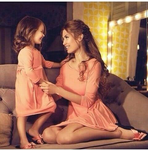 madre e hija con el mismo vestido sentadas en un sofá