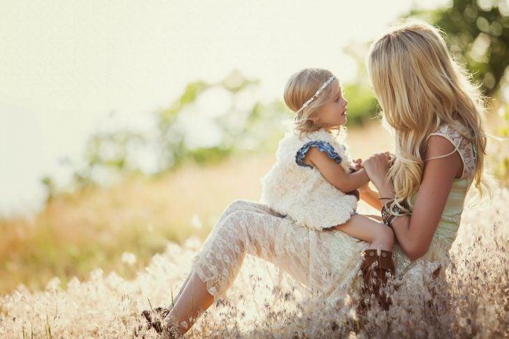 madre e hoja sentadas en el campo recargadas en un árbol