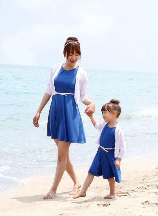 madre e hija usando el mismo vestido caminando por la playa