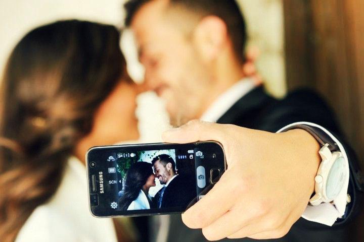 "pareja de novios tomandose ""selfie"" con su celular"
