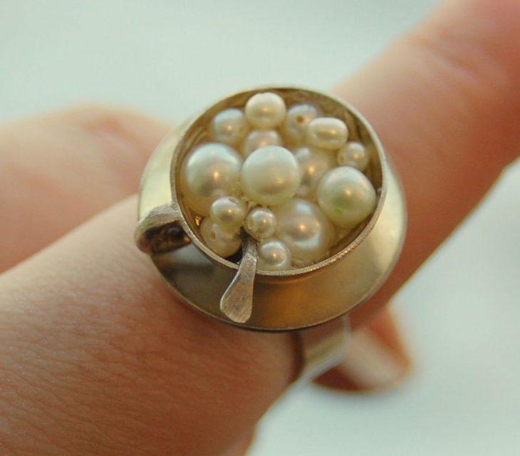 Fotografía de anillo sobre un dedo en forma de taza de capuchino con perlas en la superficie