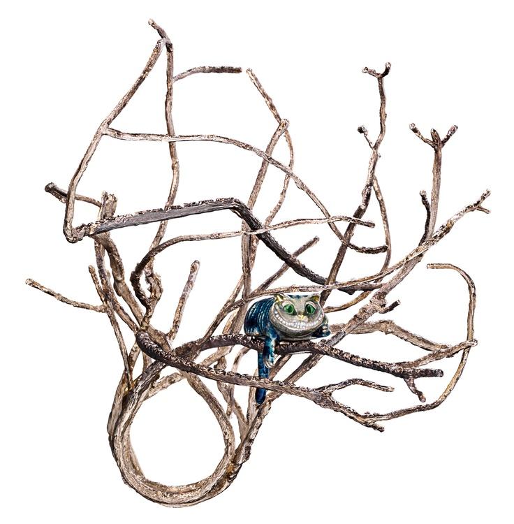 fotografía de anillo de alicia en el el país de las maravillas donde se ven las ramas de un árbol y sobre ellas esta recostado un gato