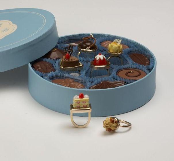 fotografía de caja de postres y chocolates en forma de anillos
