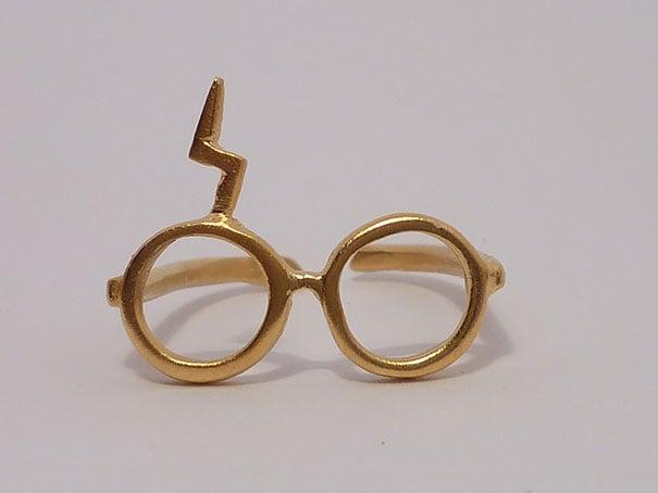 fotografía de anillo lentes de harry potter con cicatriz de rayo en colar dorado
