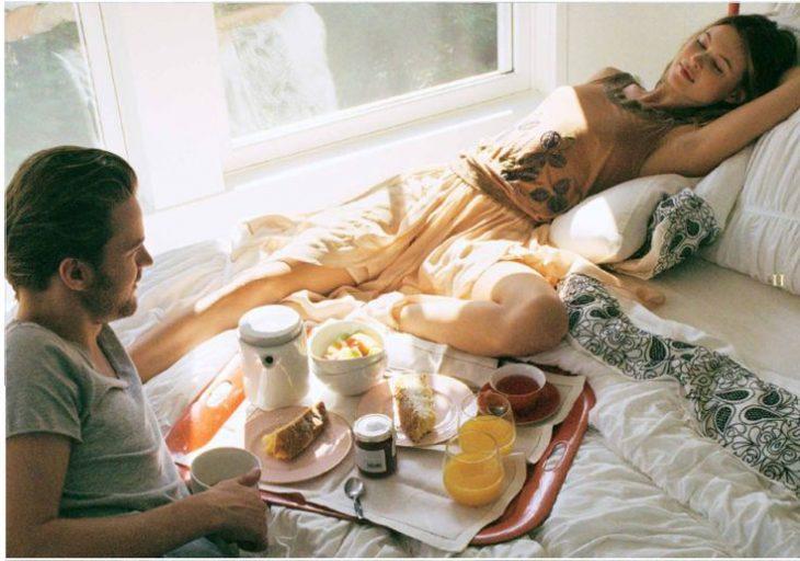 pareja de novios en la cama con el desayuno