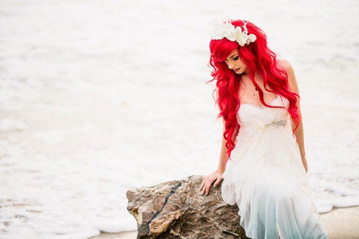 mujer con vestido blanco y azul y de cabello rojo sentada en una gran roca y tras ella se encuentra el mar