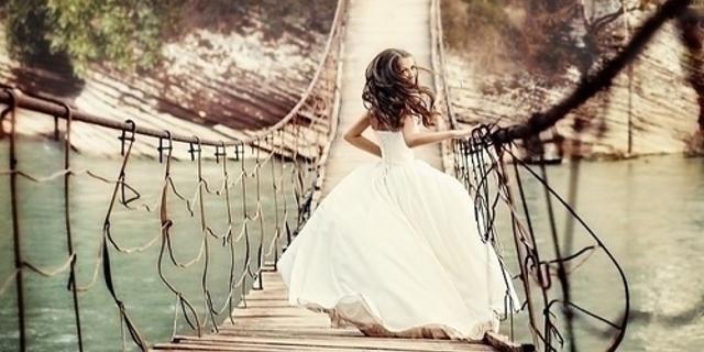 mujer corriendo con vestido de novia por un puente