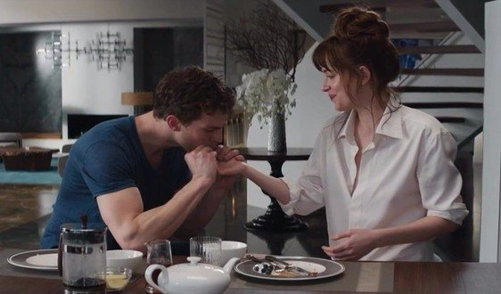 people sharing breakfast as he kisses her hand