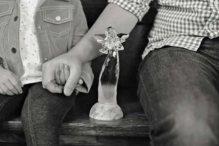 niña y su papá sentados en las escaleras con un ángel de vidrio en medio de ellos dos mientras su papá sujeta su mano