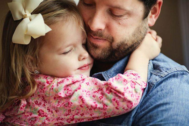 padre abrazando a su hija de manera cariñosa mientras ambos tienen los ojos cerrados