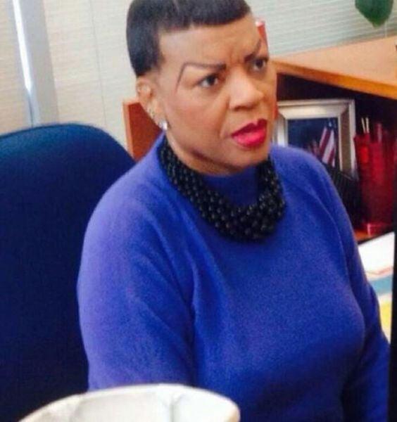 mujer sentada en un escritorio vestida de color azul con un collar en color negro