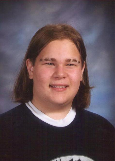 chico de cabello corto vestido con playera azul y blanca posando para el anuario