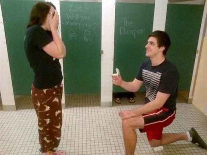dos personas en un baño publico, una parada y la otra de rodillas sosteniendo un anillo