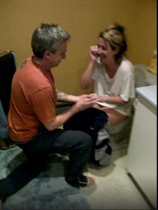 persona de rodillas y la otra en el inodoro mientras el hombre le propone matrimonio