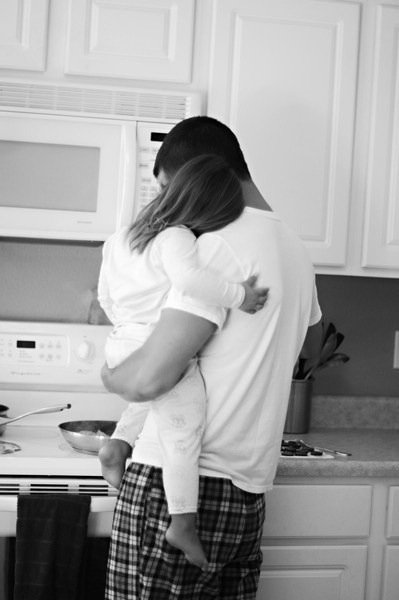 hombre sosteniendo a una niña en brazos mientras están en la cocina