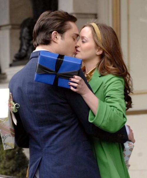 novios besandose en medio de la calle sosteniendo un regalo