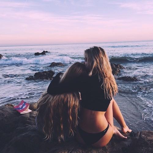 amigas abrazadas sentadas en una piedra de la playa