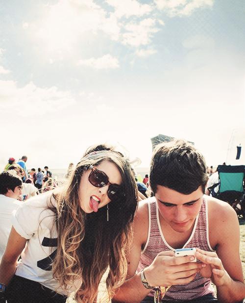 hombre y mujer sentados en una banca mientras él revisa su celular