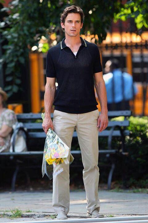 hombre parado en medio de la calle sosteniendo un ramo de flores en sus manos